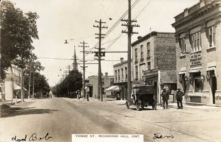 An old black and white photograph looking north on Yonge Street near the corner of Arnold Crescent featuring an old car with two men standing beside it (circa. 1915)